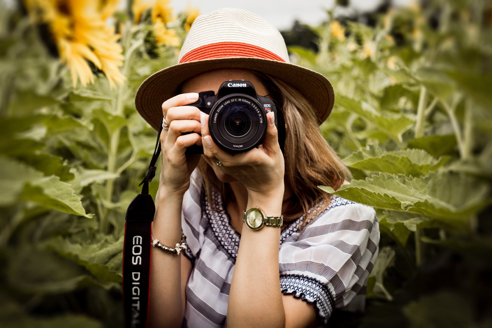 this is an image of a woman holding a dslr camera surrounded by plants