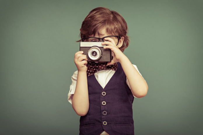 this is an image of a young boy with waistcoat and glasses taking a photo
