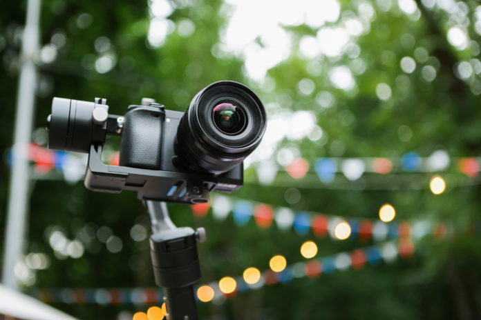 this is an image of A mirrorless camera with a stabilized monopod and remote control. On the background of the fair in the park