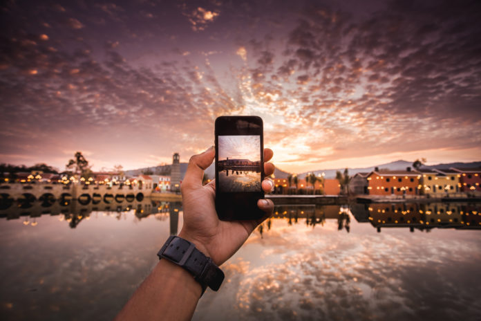 this is an image of a hand taking a photo a sunset on an iPhone
