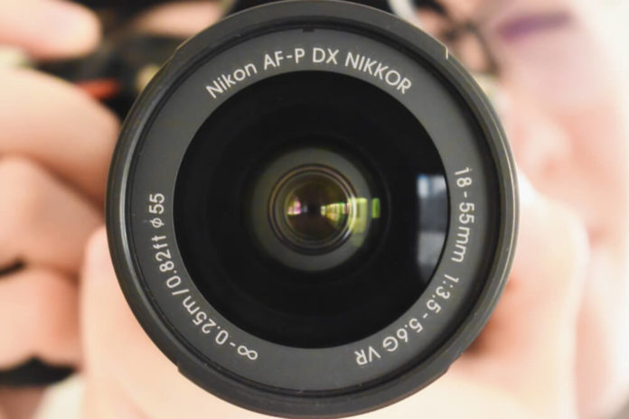 Closeup picture of the camera lens of the Nikon d5600 dslr, held by a photographer.