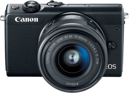 This is an image of a black Canon EOS M100 Mirrorless Camera with 15-45mm Lens - Wi-Fi, Bluetooth, 24.2-megapixel sensor and 3-inch LCD touchscreen.