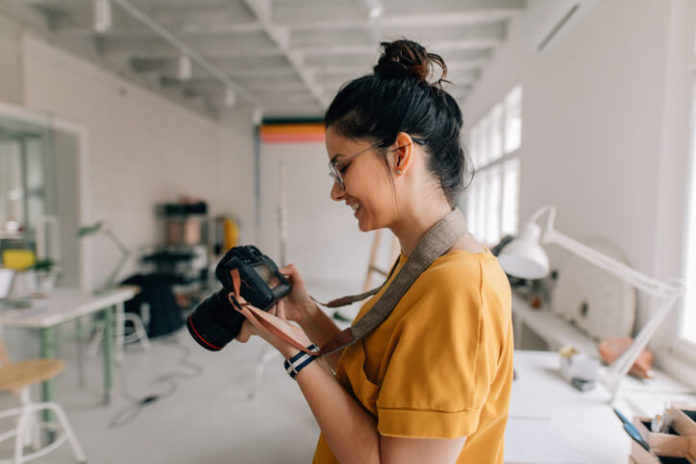 Woman holding a digital camera in her photography studio
