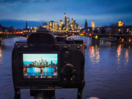 A full frame mirrorless camera being used on a tripod to capture a long exposure image of Frankfurt's cityscape, with the reflections in the river. The device screen shows the settings to be used - a 13 second exposure at F16, with an ISO of 50.