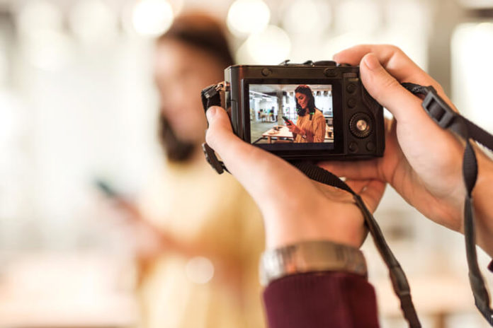 man taking a photo of a young woman using a small digital camera