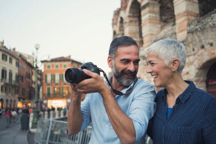 Mature couple as tourist using a camera in city Verona