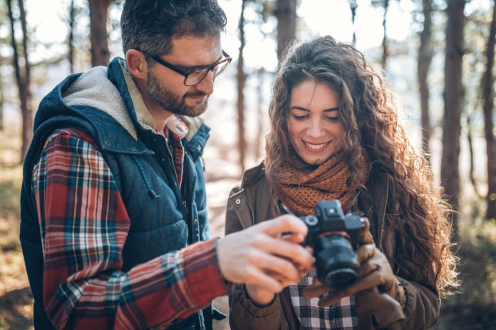 Photo of young couple with beginners camera in nature