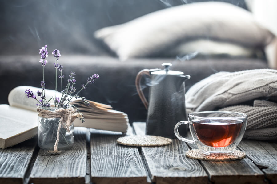 Picture of a teacup, a book and flowers on a table