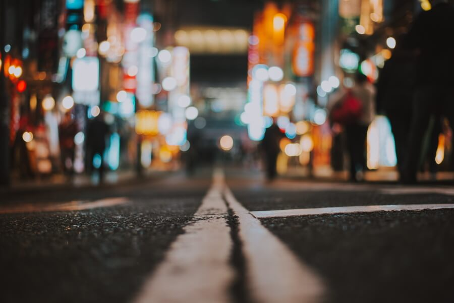 Photo at night of a street with blurred city lights