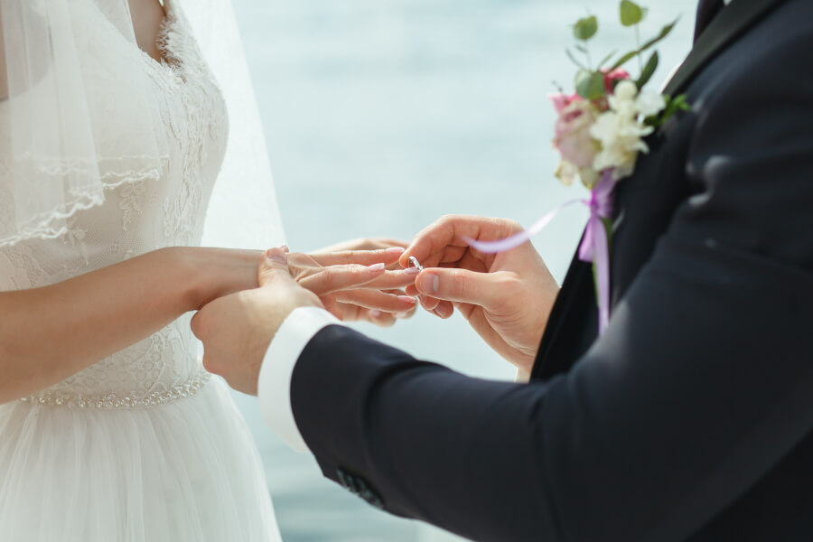 Photo of a bride receiving the ring from the groom